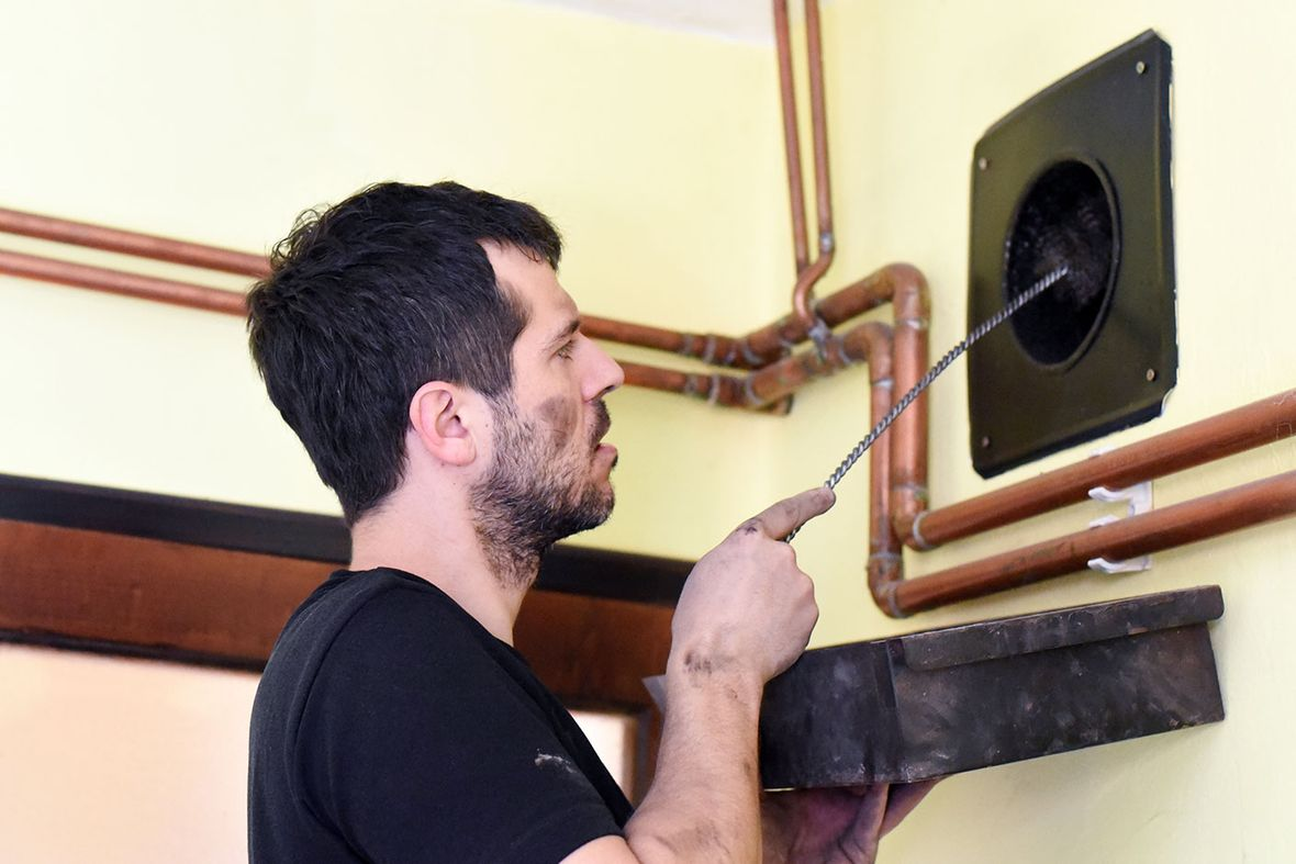 A chimney sweep cleaning out a vent